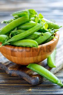 Wooden bowl with green pea pods.