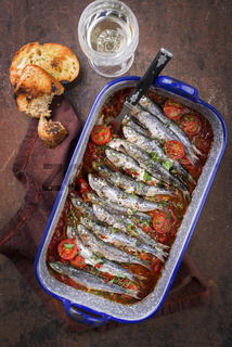 Sardinas en salsa with garlic bead as top view in a skillet
