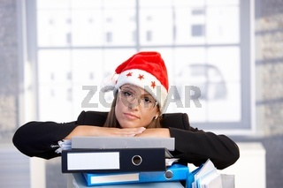 Young woman in santa hat troubled in office