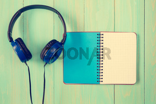 Stereo headphones and blank notebook