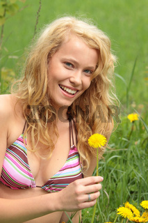 Beautiful woman relaxing in the grass and flowers