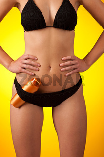 Part of female body wearing black bikini  and bottle of suntan cream