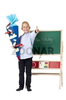 Junge mit Schultüte steht am 1. Schultag vor Tafel und zeigt Dau