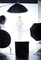 Young beautiful model posing in professionally equipped studio, waving by light fabric over white – making high key