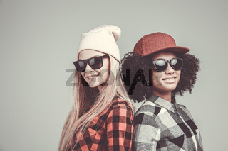 Studio lifestyle portrait of two best friends hipster girls going crazy and having great time together.