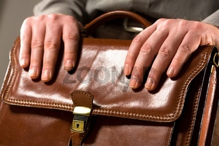 Businessman leaning on briefcase