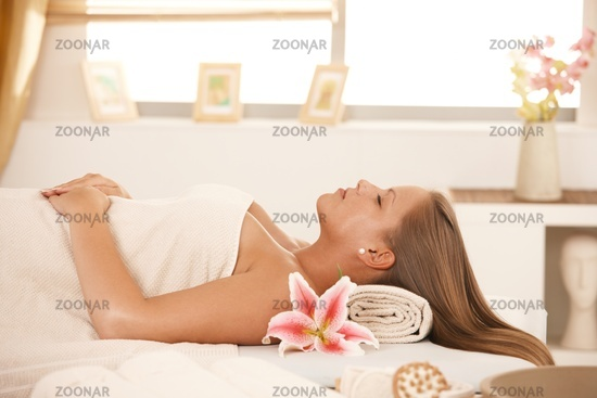 Beautiful woman sleeping on massage bed