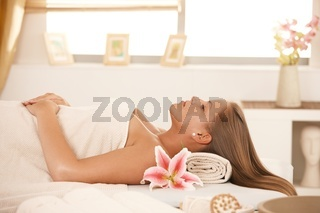 Beautiful woman sleeping on massage bed