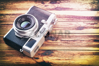 Retro vintage camera on wood table background.