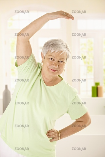 Healthy elderly woman training at home