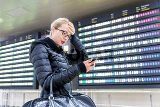 Stressed worried woman in international airport checking flight information on smart phone app.