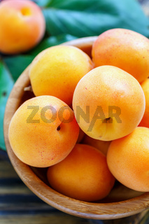 Ripe apricots in a wooden bowl closeup.
