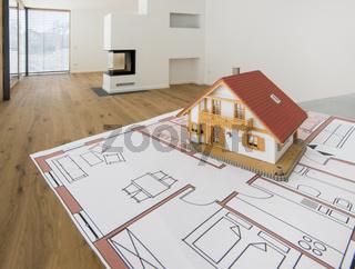 Hausbau und Planung mit Bauplan und Modellhaus in modernem Wohngebäude