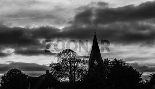 Sonnenuntergang mit Kirchturm in schwarz-weiss