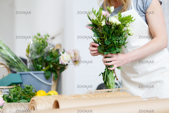 Young woman florist makes bouquet