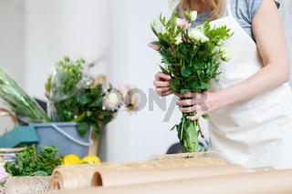 Young woman florist makes bouquet