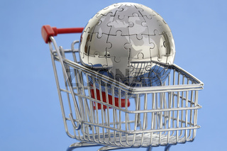 Metal puzzle globe with shopping cart on blue background