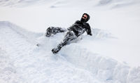 Man is falling into deep snow. Concept of winterly slippery conditions.