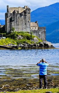 Mann fotografiert Schloss Eilean Donan, Schottland, Grossbritannien