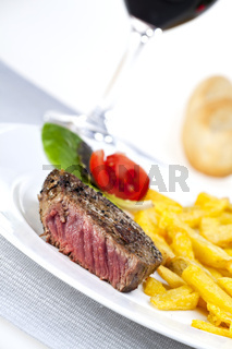 closeup of a beef steak with french fries on a white background