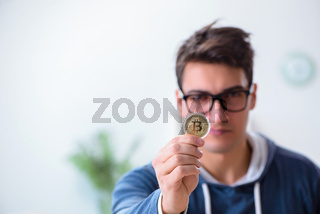 Young man mining bitcoins at home