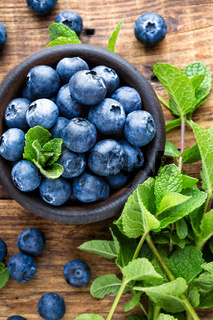 Fresh blueberries in bowl on wooden table