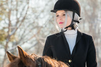 Portrait of young girl jockey riding a horse in winter forest