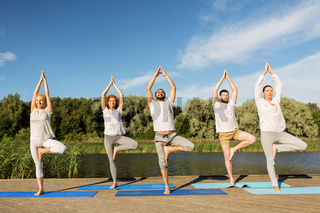 people making yoga in tree pose on mat outdoors