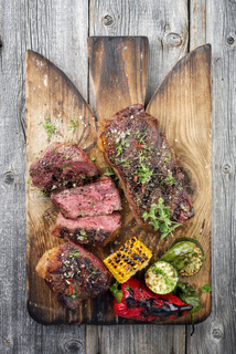 Two barbecue dry aged Kobe roast beef with vegetable as close-up on a cutting board