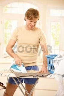 Cheerful guy ironing