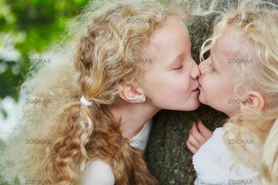Zwei kleine Mädchen küssen sich