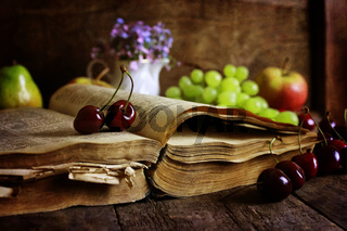 book on wooden background and cherry berry