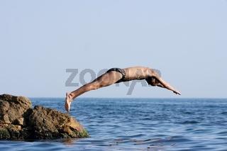 Man jumping headlong into the see