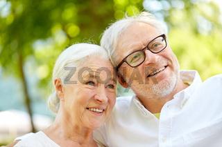 happy senior couple taking selfie at summer park