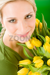 Young happy woman hold yellow tulips flower