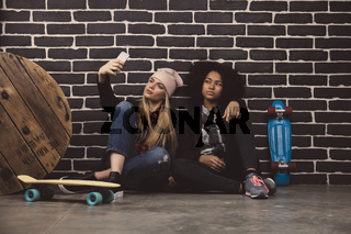 Lifestyle portrait of two hipster girls. They sit on the floor in front of a black brick wall and make selfie.