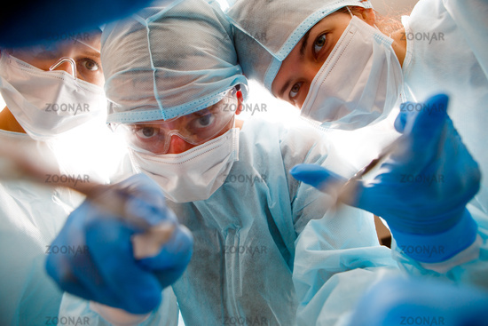 Surgeons holding instruments in hands