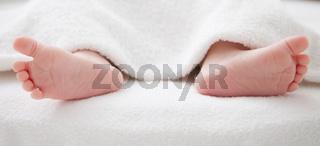 Baby feet under white blanket cover