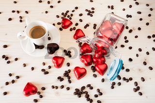 Red chocolate hearts in a glass jar and a cup of espresso coffee