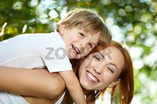 Small son piggyback on mother in a summer garden