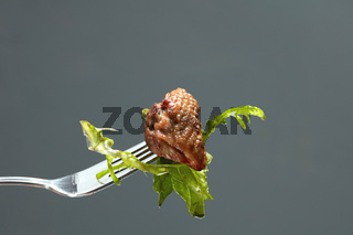 meat and salad on a fork