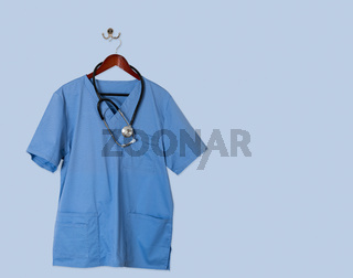 Blue scrubs shirt for medical professional hanging on blue wall