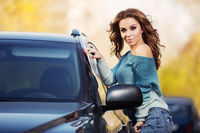 Young fashion woman with long curly hairs standing next to her car outdoor
