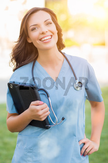 Portrait of An Attractive Young Adult Woman Doctor or Nurse Holding Touch Pad Outside.