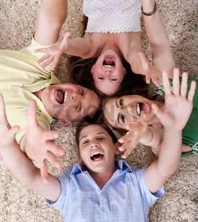 Portrait of happy family lying on carpet with their heads close together and shouting