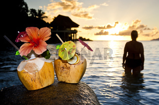 Frau steht im Sonnenuntergang vorne Kokusnüsse