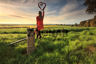 Escape to the Country - female on fence with love heart in morning light