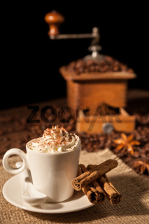 Coffee cup with whipped cream and coffee grinder on background