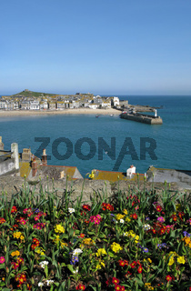 St. Ives harbour with colourful spring flowers in the foreground.