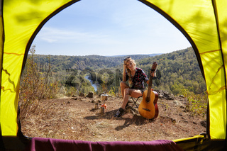 Young blonde woman tourists with guitar in camp on cliff over river and forest landscape